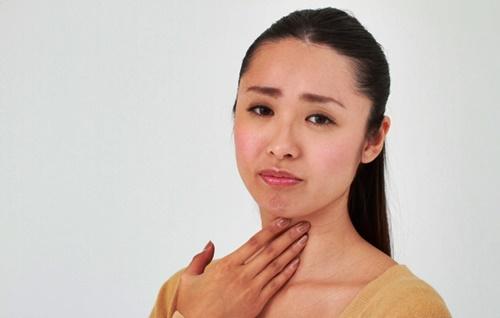 秋の花粉症でのどがイガイガする女性