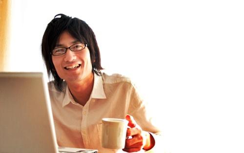 パソコンの前でお茶を飲む笑顔の男性