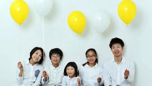 パパとママと3人子供たちが風船を持って笑顔