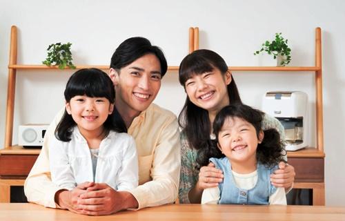 パパとママと小さな女の子2人笑顔で団らん