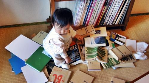 本棚の本を散らかす男の赤ちゃん