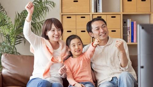 笑顔のパパとママと一人娘がテレビ鑑賞