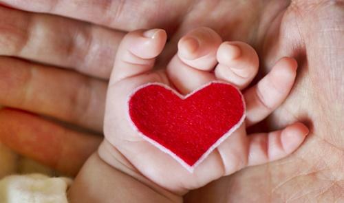 かわいい赤ちゃんの手のひらに赤いハート