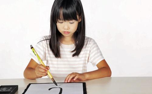習字教室で習字を書く女の子
