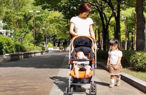 乳母車の赤ちゃんと散歩するママと小さな女の子
