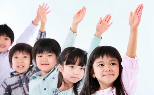 大人数制の学習塾で手を挙げている小学生たち