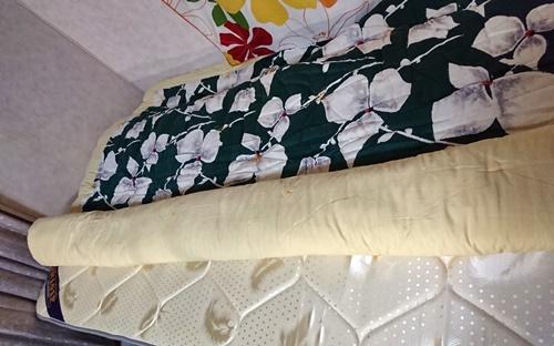 狭いベッドを広げるために掛布団を巻く