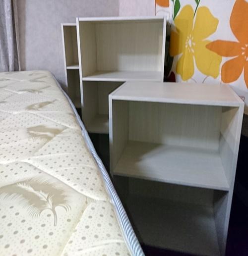 ベッドの近くにカラーボックスが3つ