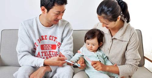 赤ちゃんに歯磨きを教えるパパとママ