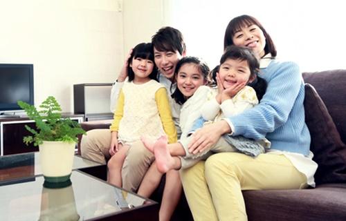 自宅の居間で3人子どもを抱っこするパパとママ