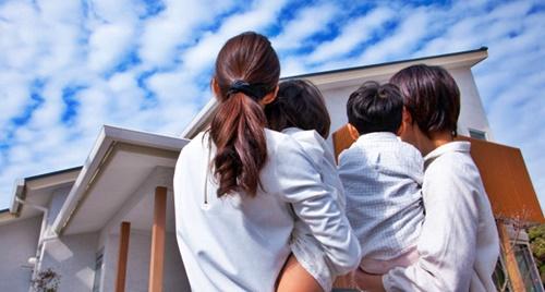 2人の子どもを抱っこして自宅を見るパパとママ