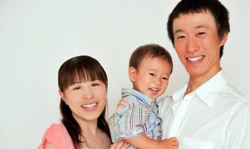 幼い男の子を抱っこするパパとママ