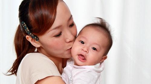 赤ちゃんのほっぺにキスをするまま