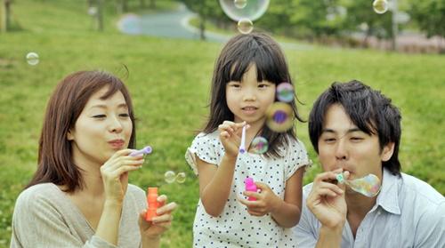 パパとママと一緒にシャボン玉をする女の子
