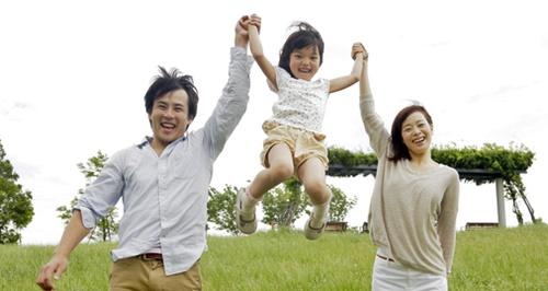 パパとママと草原で遊ぶ女の子