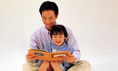 パパに絵本を読んでもらって嬉しい女の子