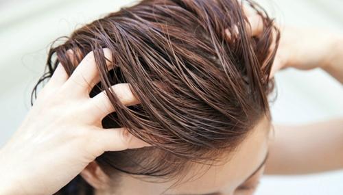 ヘアカラートリートメントを髪になじませる女性
