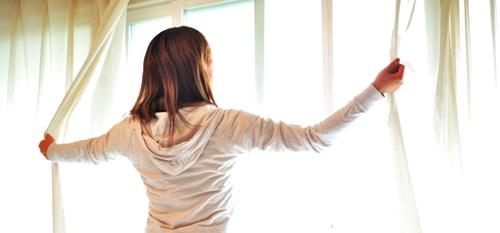 カーテンを開けて朝陽を取り込むママ