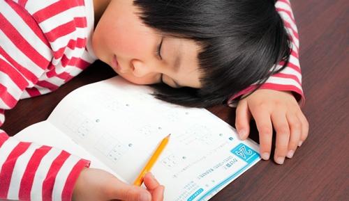 寝不足で授業中に居眠りをする小学生